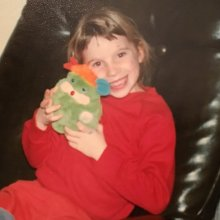 Caitlin as a child hugging a stuffed toy