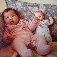 Bliss as a baby sitting with a doll